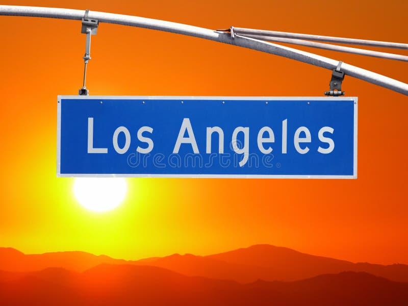 洛杉矶与圣塔蒙尼卡山日落的路牌 库存照片