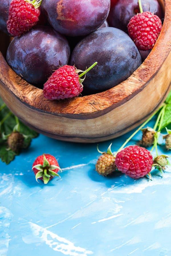 李子和红草莓特写镜头静物画与绿色叶子 免版税库存照片