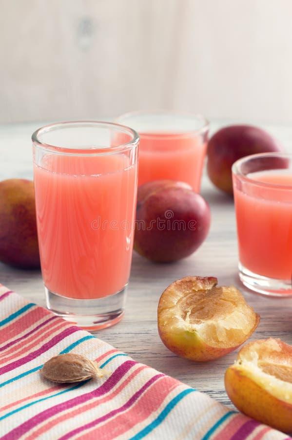 李子汁 在一张白色木桌上的桃红色饮料与镶边餐巾 图库摄影