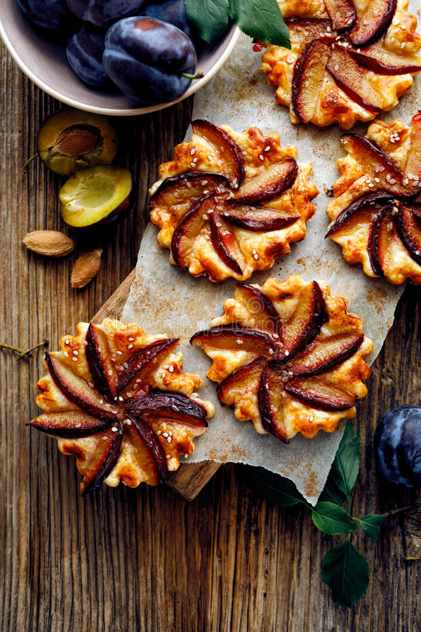 李子馅饼用在木桌、可口点心用油酥点心和果子上的桂香 库存照片