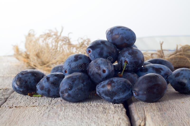 李子 在木桌上的蓝色和紫罗兰色李子 免版税库存照片