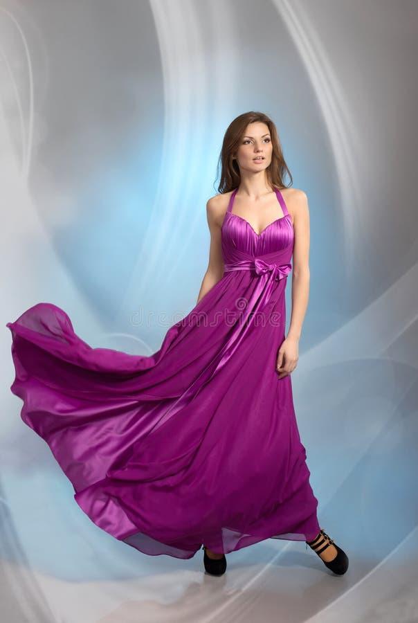 李子紫罗兰色晚礼服的美丽的女孩 免版税库存图片