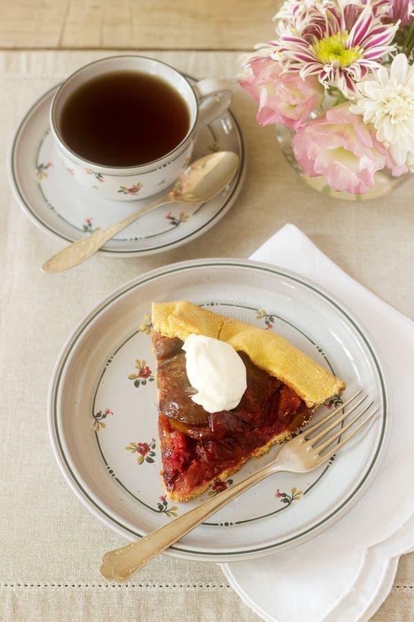 李子galett片断与奶油和茶的 点心 土气样式,选择聚焦 图库摄影