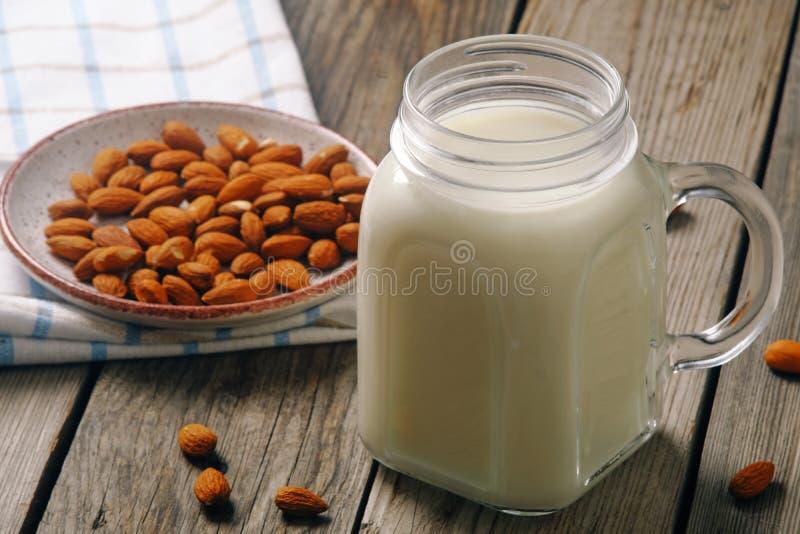 杏仁在瓶子的牛奶鸡尾酒有在土气木桌上的杏仁坚果的 素食主义者供选择的食物,不含乳制品的牛奶,干净的吃概念 免版税库存图片