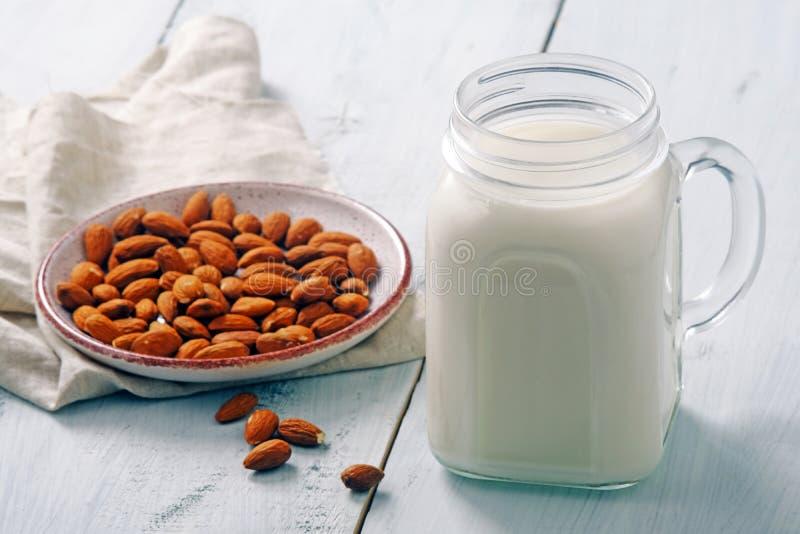 杏仁在瓶子的牛奶鸡尾酒有在土气蓝色木桌上的杏仁坚果的 素食主义者供选择的食物,不含乳制品的牛奶,干净吃 免版税库存图片