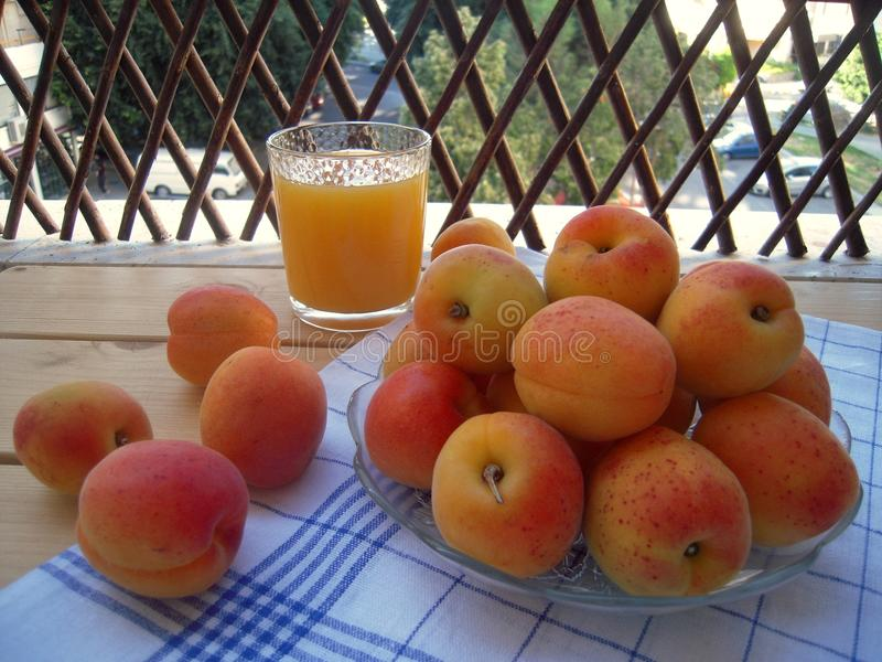 杏子成熟和甜在厨房餐巾和一杯汁液 免版税库存图片
