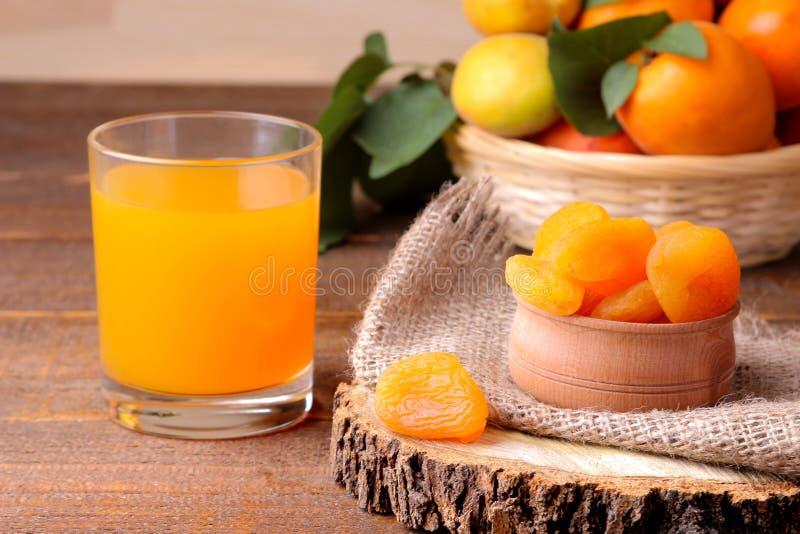 杏干、杏子汁和新鲜的杏子在棕色背景 库存图片