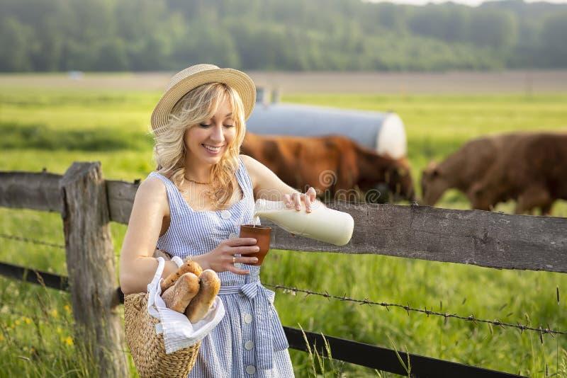 村庄女孩倾吐的牛奶到一块玻璃里,在领域背景与吃草母牛的 夏天农村生活在德国 免版税库存照片