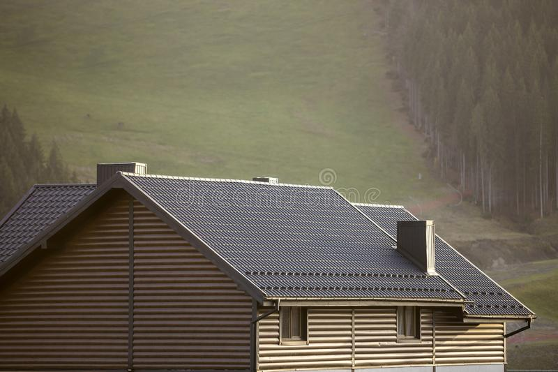 村庄屋顶与侧面墙的,棕色木瓦屋顶和高烟囱在生态区域在有雾的风景拷贝空间 库存照片