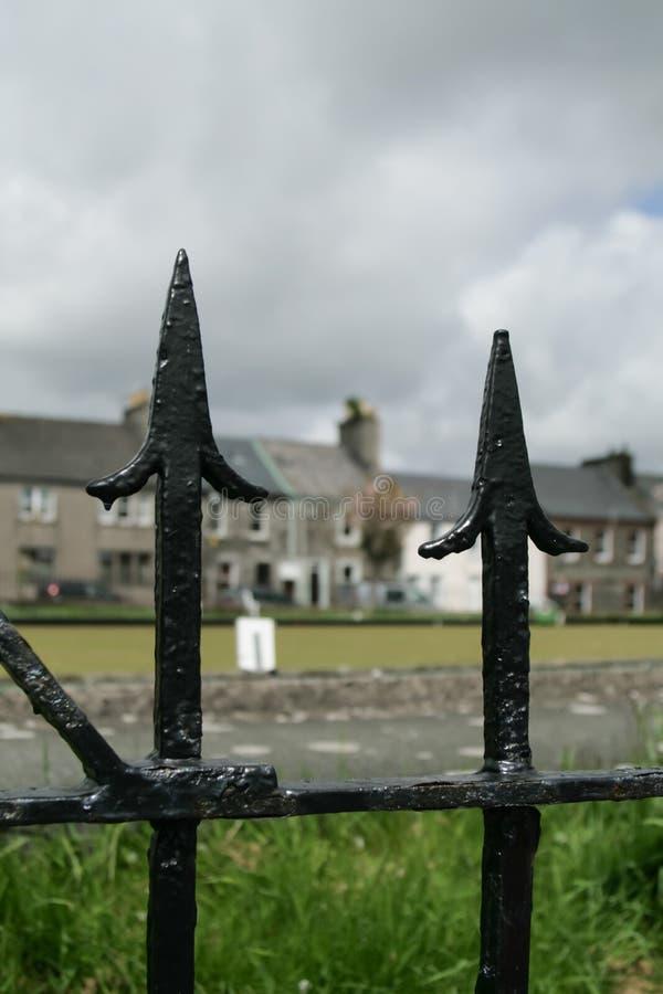 村庄广场和露台的房子通过黑金属篱芭 库存图片
