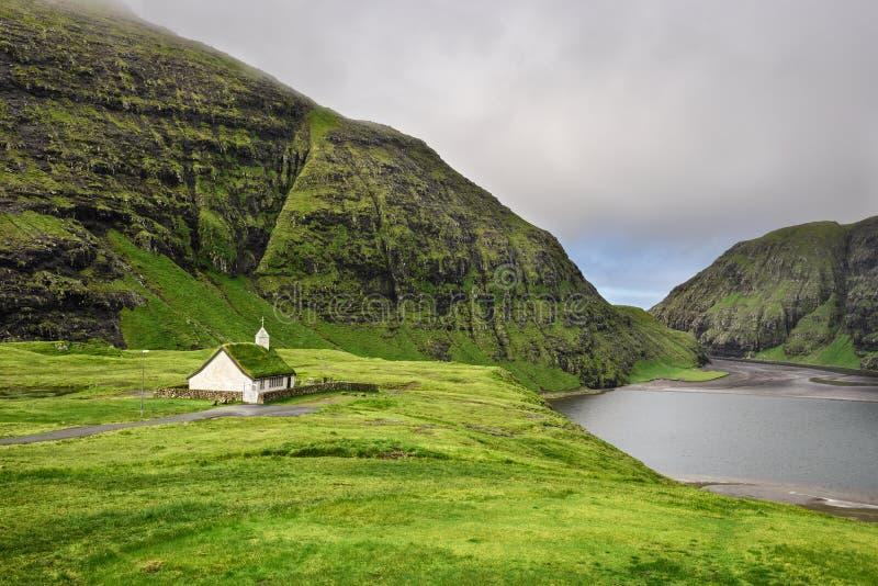 村庄教会和一个湖在Saksun,法罗群岛,丹麦 免版税库存照片