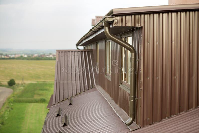 村庄用棕色金属房屋板壁板条和墙壁盖的顶楼室、屋顶,新的天沟系统 图库摄影