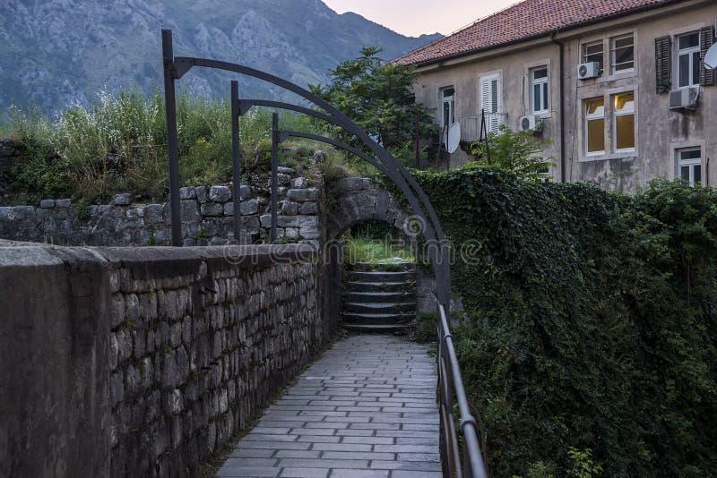 村庄的晚上视图,梯子被缠绕标尺和篱芭的,石墙 以高山为背景 库存图片