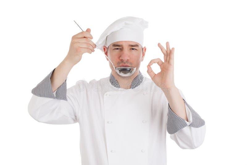 从杓子的年轻厨师品尝食物 免版税库存图片