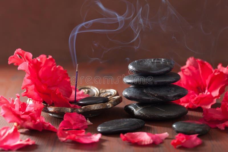 杜娟花开花aromather的黑按摩石头香火棍子 库存照片