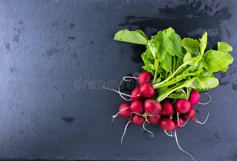 束与叶子的萝卜在黑暗的背景 免版税图库摄影