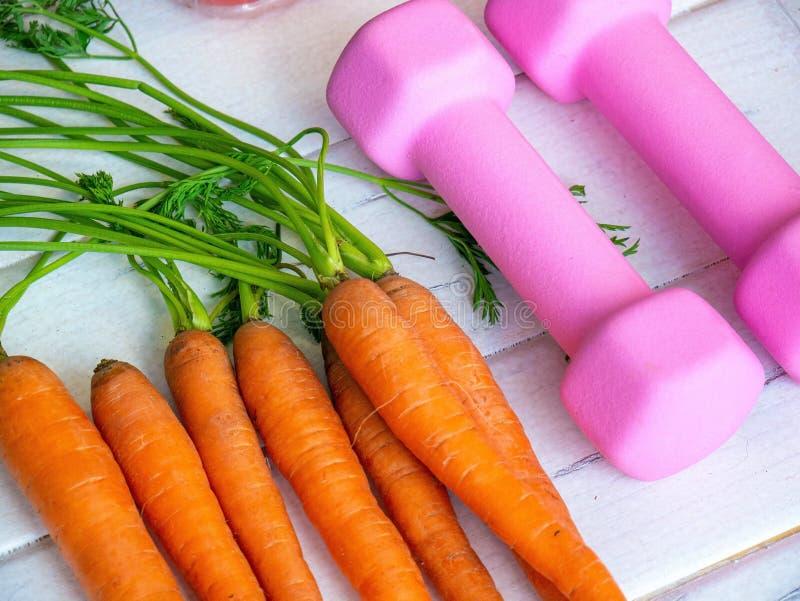束与哑铃的新鲜的红萝卜 健康的,动脉压,体育的正常化概念红萝卜 免版税库存图片