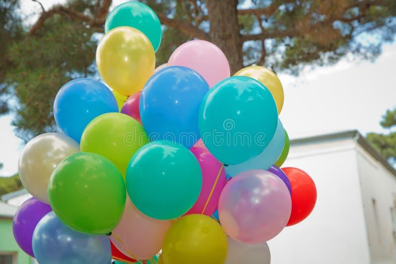 束五颜六色的气球在绿色背景中 室外党的许多五颜六色的气球 飞行Colorfull的气球  免版税库存照片