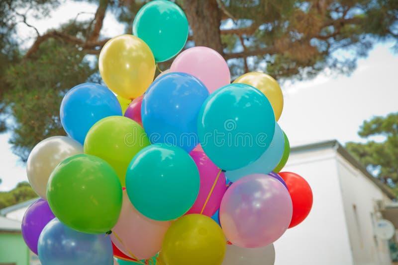 束五颜六色的气球在绿色背景中 室外党的许多五颜六色的气球 飞行Colorfull的气球  免版税库存图片