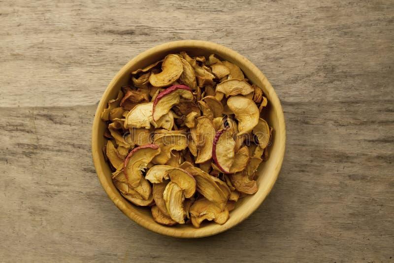 束在一个碗的干苹果在老木背景 免版税库存照片