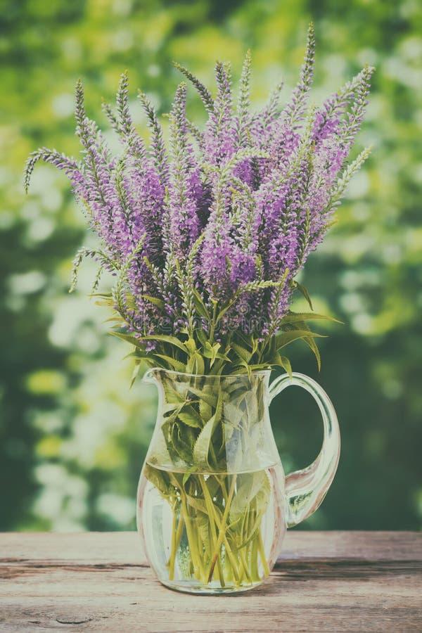 束在一个水罐的野花在老木桌上 免版税图库摄影