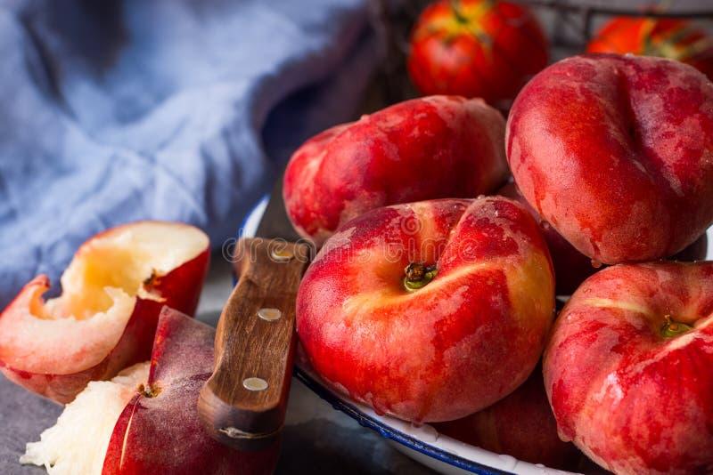 束在白色板材的成熟有机五颜六色的红色土星桃子,被对分,刀子,蓝色餐巾 免版税库存照片