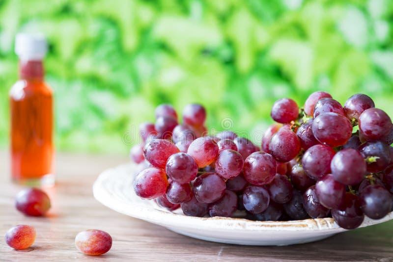 束在白色板材的红葡萄,反对绿色叶子背景 文本的空间 免版税库存照片
