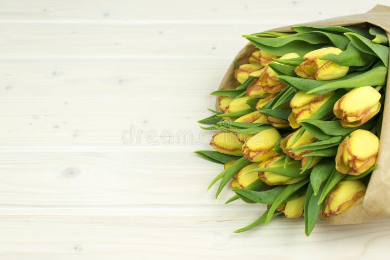 束在纸wraped的一张木桌上的黄色郁金香 免版税库存图片