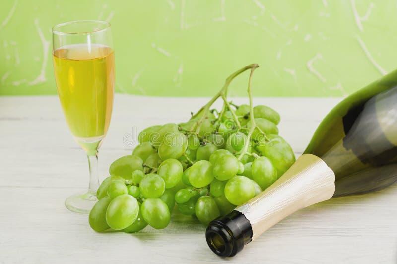 束在透明和易碎玻璃的新鲜的成熟绿色葡萄充分酒和一个附近打开了在老木板条的瓶 库存照片