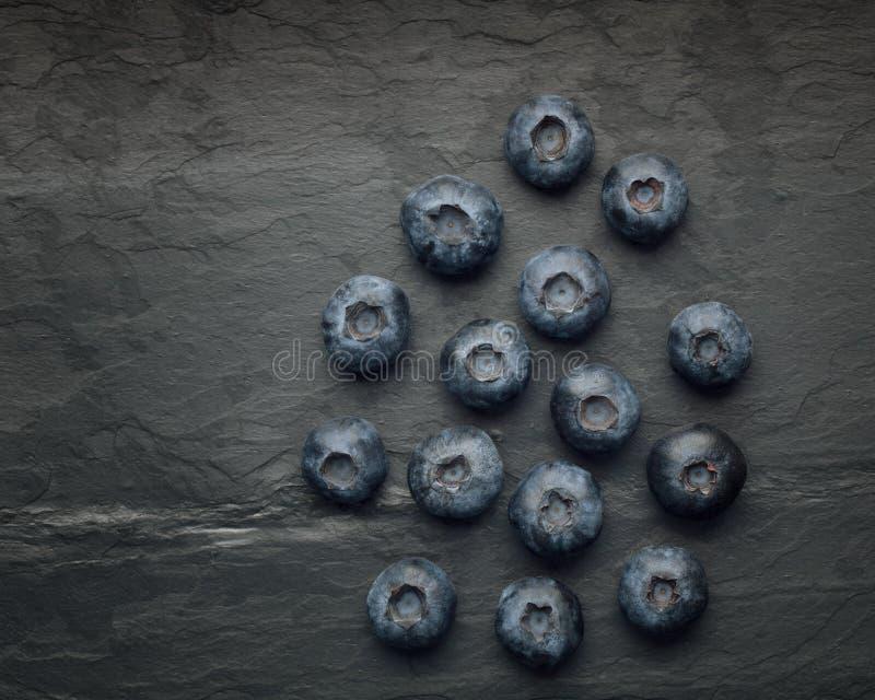 束在黑暗的葡萄酒板岩的可口蓝莓 免版税库存照片
