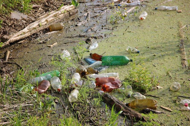 束塑料瓶被投掷入水 垃圾,废物,环境污染 免版税库存照片