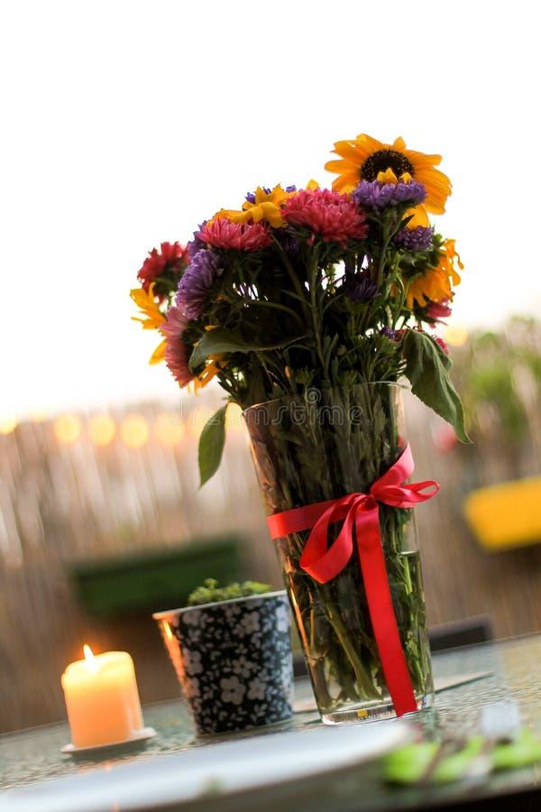 束夏天花和在大阳台的一个burrning的蜡烛 图库摄影