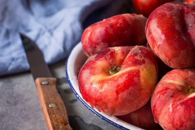 束成熟有机五颜六色的红色土星桃子用水在白色板材,刀子,蓝色餐巾,黑暗的厨房用桌下降 免版税库存照片