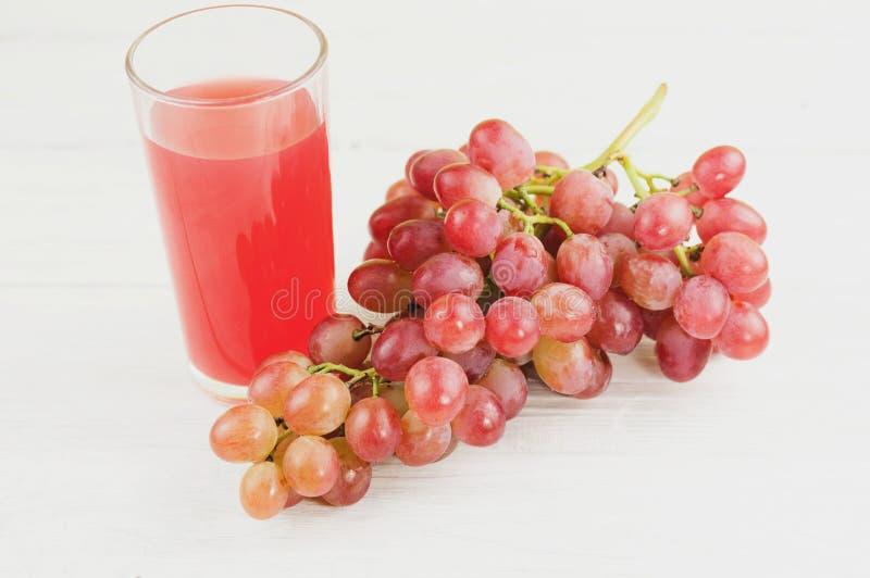 束新鲜的成熟玫瑰色葡萄充分临近透明和易碎玻璃在老木白色板条的汁液 库存照片