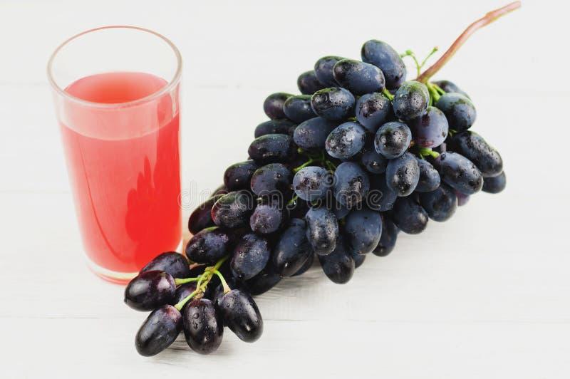 束新鲜的成熟蓝色葡萄充分临近透明和易碎玻璃在老木白色板条的汁液 库存照片