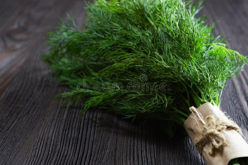 束新鲜的莳萝和香料在黑暗的木背景 库存图片