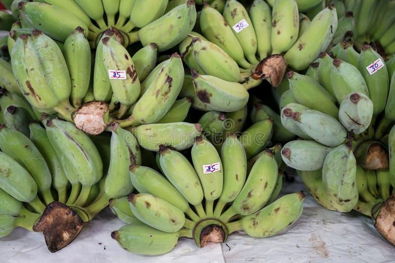 束未加工的绿色在地方市场上耕种了香蕉与价牌 免版税库存照片