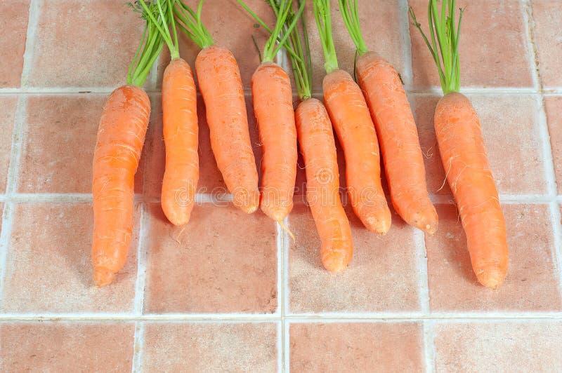 束红萝卜在厨房里,瓦片背景的 免版税库存图片