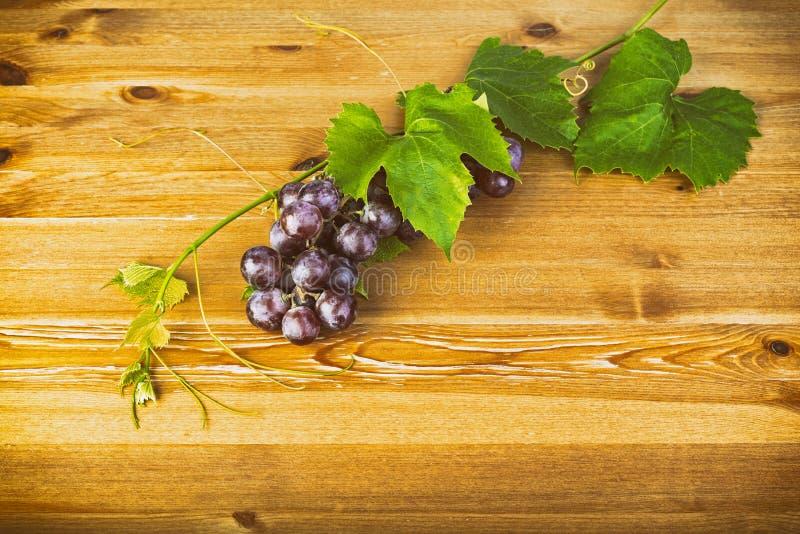 束红葡萄和叶子在木桌上 库存照片