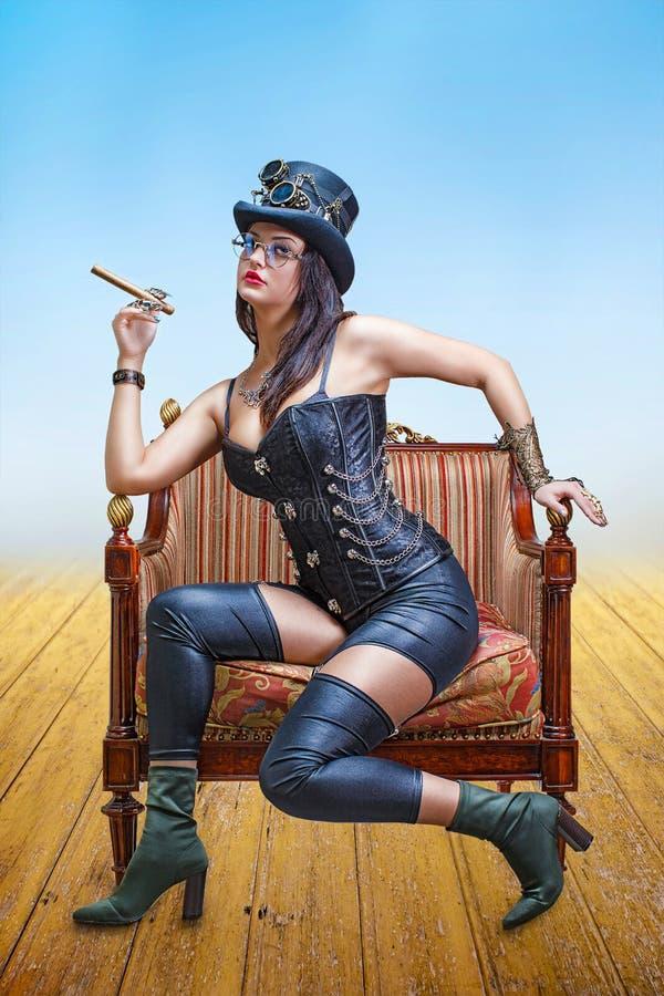 束腰、浅顶软呢帽帽子和steampunk焊接的玻璃的美丽的女孩,与雪茄在她的手上 免版税库存照片