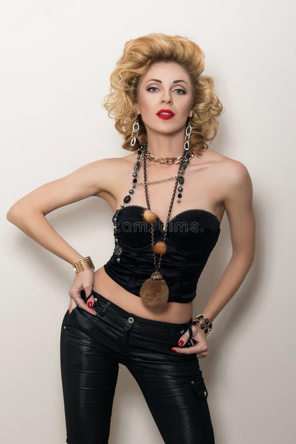 黑束腰和皮革长裤的性感的白肤金发的妇女 免版税库存图片