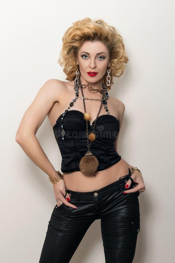 黑束腰和皮革长裤的性感的白肤金发的妇女 免版税库存照片