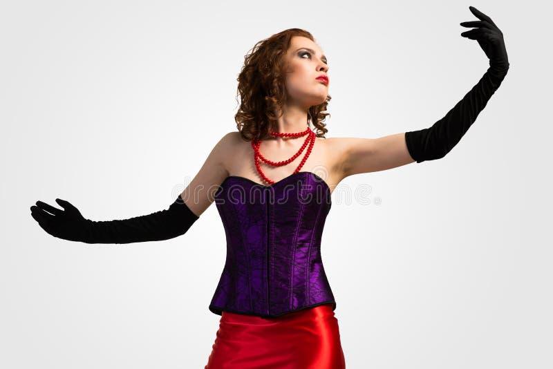 束腰和红色礼服的年轻可爱的妇女 免版税图库摄影
