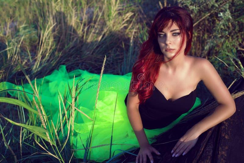黑束腰和长尾巴绿色遮掩的美丽的红发妇女避开倾斜在破旧的颠倒的木小船 库存图片