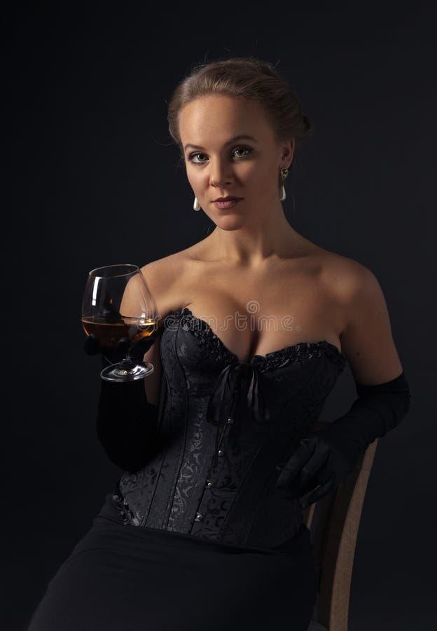 黑束腰的年轻美丽的妇女有杯的白兰地酒 免版税库存图片
