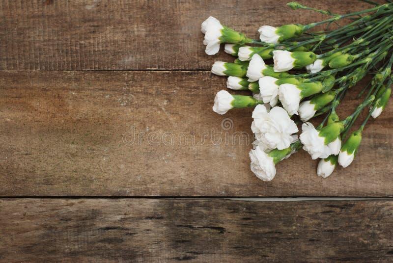 束起白色康乃馨花花束安排构成被隔绝的土气木背景 免版税库存图片