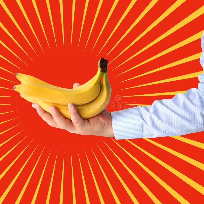 束香蕉在手中在太阳风格化背景  流行艺术 图库摄影