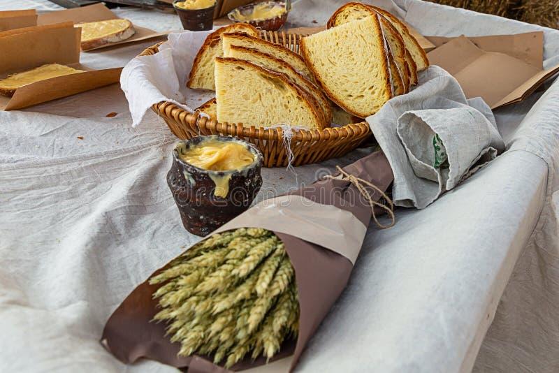 束麦子的耳朵在牛皮纸的一碗蜂蜜农厂柜台的面包篮子自然村庄午餐 图库摄影