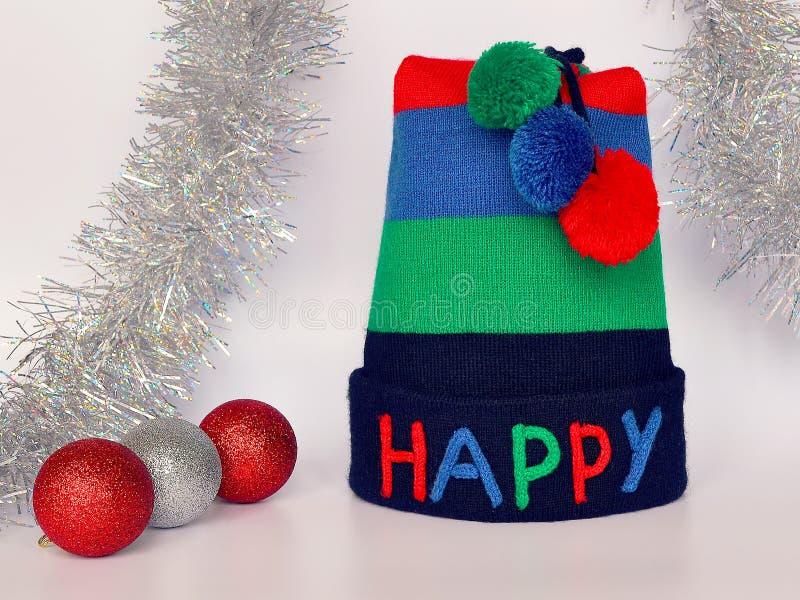 条纹有多彩多姿的愉快的词和三大型机关炮、红色和银色圣诞节球和银色闪亮金属片的编织帽子在中性 免版税库存图片