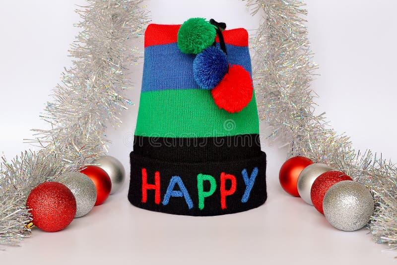 条纹有多彩多姿的愉快的词和三大型机关炮、红色和银色圣诞节球和银色闪亮金属片的编织帽子在中性 免版税库存照片